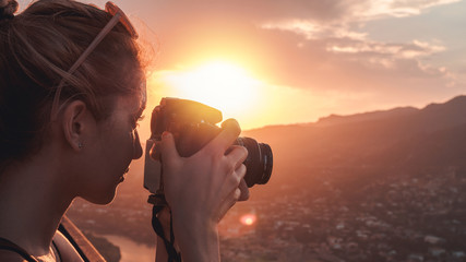 Wall Mural - Female photographer, taking pictures of mountain landscape at sunset