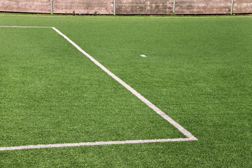 Part of sport soccer stadium and artificial turf football field. Detail, close up of green grass with white lines, goal line, corner line. Focus football field selected background, texture, wallpaper.