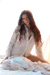 langhaarige brünette Frau in weißem Hemd im Bett