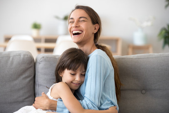 Cheerful mom laughing embracing cute kid daughter, loving mother mum and happy little girl hugging cuddling together sitting on sofa, funny mommy and child having fun good time at home concept