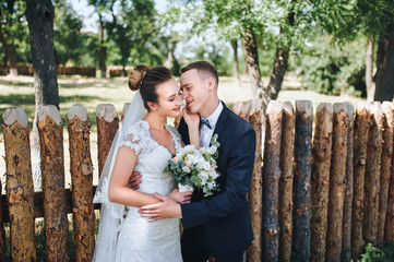 Lovely newlyweds stand in nature, against the background of wooden stakes, in sunny weather. Stylish groom embraces a beautiful bride in a lace dress in a green garden. Wedding photography.