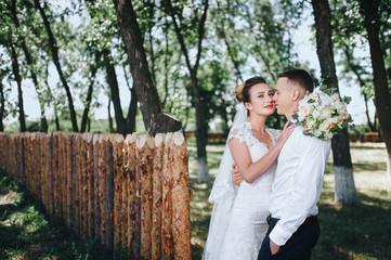 Newlyweds in love stand on the nature, against the background of wooden stakes, in sunny weather. Stylish groom embraces a beautiful bride in a lace dress in a green garden. Wedding photography.