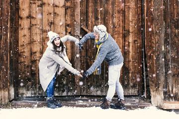 Verliebtes Paar im Winter Valentinstag machen ein Herz mit den Armen