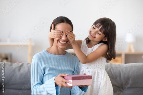 Smiling Child Daughter Closing Eyes Of Excited Mom Holding Pink Gift Box Congratulating Mum Celebrating Birthday