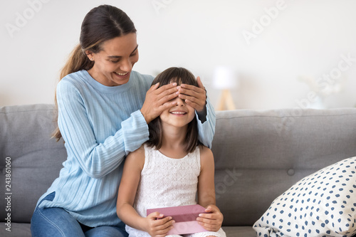 Caring Mother Closing Eyes Of Excited Kid Daughter Holding Pink Gift Box Sitting On Sofa At