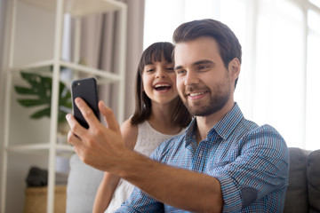 Smiling father taking selfie with cute kid on smartphone posing for self portrait, happy dad laughing making photo with little daughter at home, single daddy and child playing having fun with phone