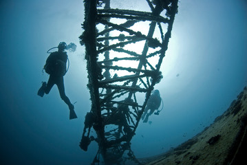 Scuba Divers on a ship wreck in clear blue water with sun in the background