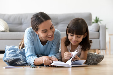 Caring smiling mother reading book with little kid girl lying on warm floor at home, mom or baby sitter playing having fun telling fairy tale to child daughter, underfloor heating, family activities