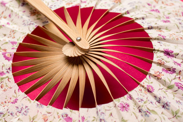 Traditional fan with far eastern motive on red background close up.