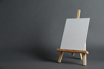 Wooden easel with blank canvas board on dark background, space for text. Children's painting