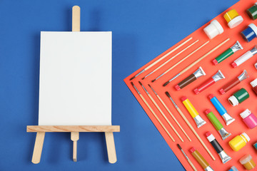 Flat lay composition with set of painting tools for children on color background
