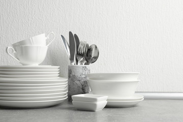 Set of clean dishes and cutlery on table near light wall. Space for text Wall mural
