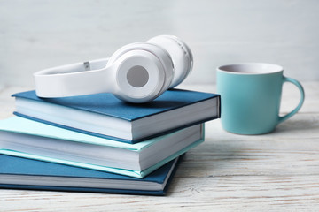 Modern headphones with hardcover books on wooden table. Space for text