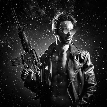 A man in a leather jacket and glasses poses with an automatic rifle.