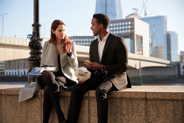 Two millennial colleagues take a break sitting on the embankment eating near London Bridge by the River Thames, close up
