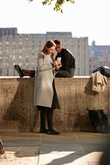 Two female friends taking a break on the embankment by the River Thames, looking at a smartphone, backlit