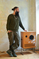 Stylish male with piercings standing near a custom made loudspeaker