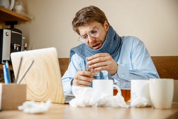 Sick man with pills working in office, businessman caught cold, seasonal flu. Pandemic influenza, disease prevention, illness, virus, infection, temperature, fever and flu concept