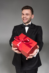happy elegant man in black tuxedo and tie bow gifting red present isolated on grey
