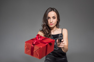 serious brunette woman holding red present and gun isolated on grey