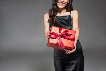 cropped view of happy woman holding red gift box isolated on grey