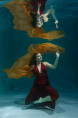 beautiful free diver woman swimming in long red evening dress under water alone in the deep