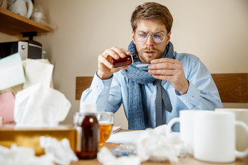 Sick man with medicinal mixture working in office, businessman caught cold, seasonal flu. Pandemic influenza, disease prevention, illness, virus, infection, temperature, fever and flu concept