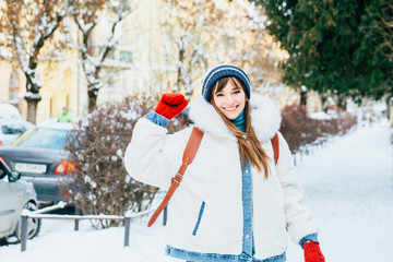 Gorgeous female say good bye on snowy street in good mood. Outdoor photo of glad woman in knitted red mittens, white fur jacket having fun during winter photoshoot before christmas.