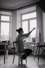 A young woman artist sits in a bright studio on a blue chair and paints a picture in oil on the easel. The woman loose comfortable casual clothing. Vertical black and white.photo.