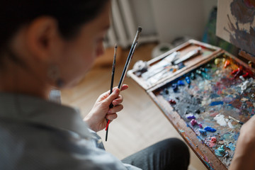 A young woman artist in her studio is holding a brush.