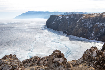 Cracks on the surface of the blue ice. Frozen lake in winter mountains. It is snowing. Lake Baikal. Winter
