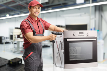 Young male worker with a drill and oven looking at the camera