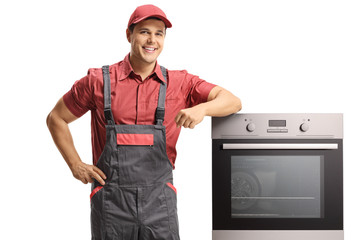 Young smiling handyman in a uniform standing next to an electric oven