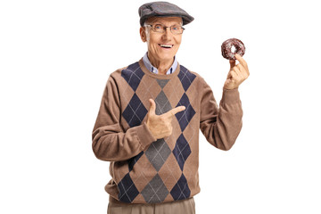 Cheerful senior man holding a chocolate donut and pointing at it