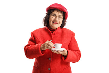 Elderly woman in a red coat standing and drinking an espresso coffee