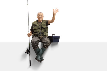 Mature fisherman with a fishing rod sitting on a panel and waving