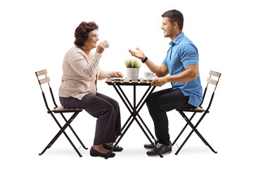 Elderly woman and a young man chatting and drinking coffee