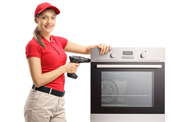 Woman from a repairing service with a drill and oven looking at the camera