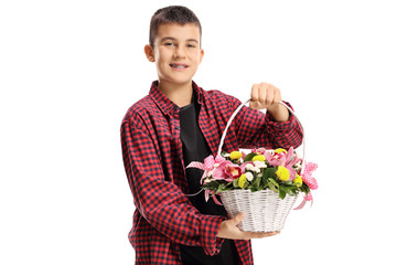 Young boy holding a white basket with orchids and other flowers