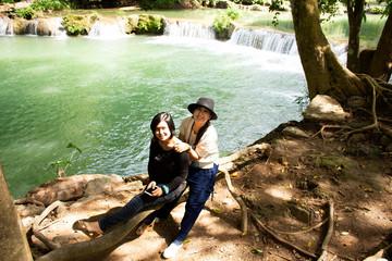 Traveler thai woman travel and posing for take photo at Chet Sao Noi small waterfalls or Namtok Chet Sao Noi National Park at Muak Lek District in the Saraburi Province of Thailand.