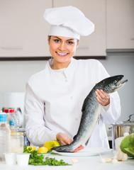 Female cook preparing big fish