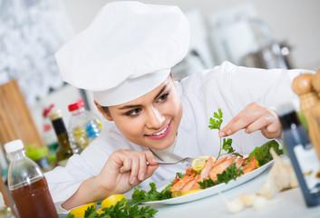 Positive female cook decorating prepared dish of shrimps