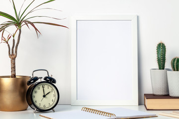 A white desk at home with plants in pots and a white mockup frame. Cactuses and yuka in a golden casing. Hipster decoration. A place for your text or graphics. Opened notebook, book and retro clock