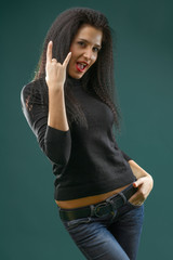 Brunette girl wearing casual outfit, jeans and black shirt, standing against bluish background, studio shot
