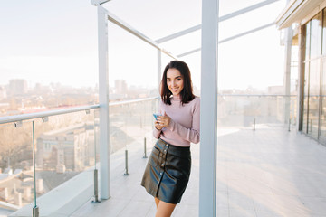 Big city life, sunny morning of young joyful woman smiling to camera on terrace in penthouse on cityview background. Fashionable model, charming businesswoman, using phone, happiness