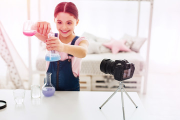 Smiling little blogger using camera stand while filming chemistry experiment