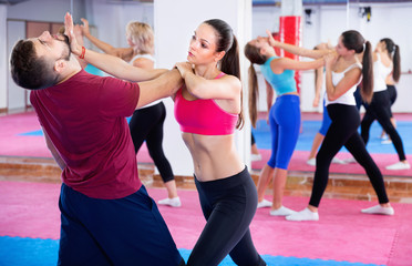 Sporty girl with her instructor are training self-defence moves in gym.
