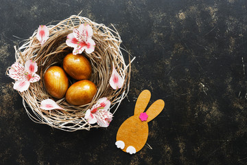 Easter golden eggs and a rabbit in a nest decorated with pink flowers on a brown dark background. Top view, place for text.