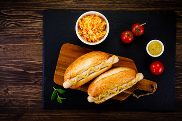 Hot dogs on cutting board on black stone plate