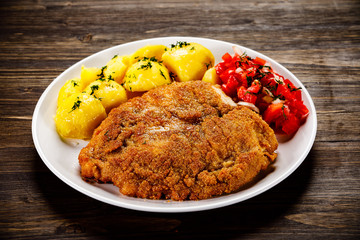 Fried pork chop, boiled potatoes and vegetable salad